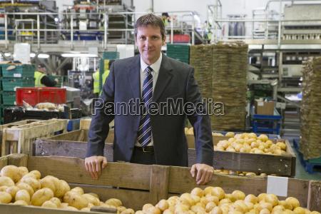 portrait confident businessman leaning on bin
