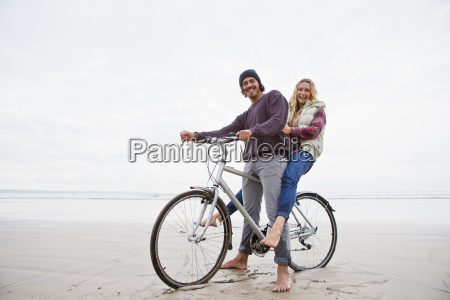 portrait smiling couple sharing bicycle on