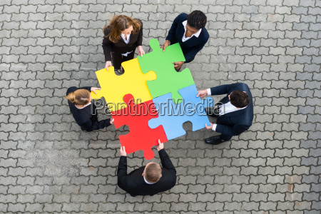 businesspeople holding colorful puzzle pieces