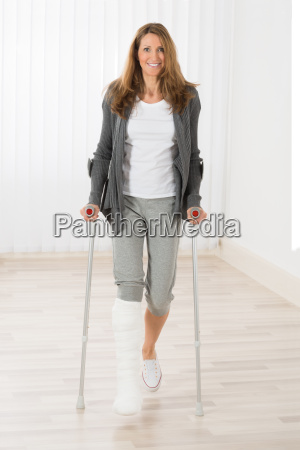 woman holding crutches while walking