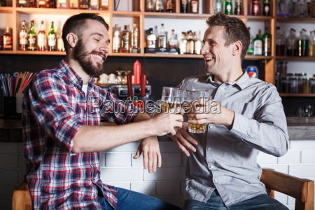 happy friends drinking beer at counter