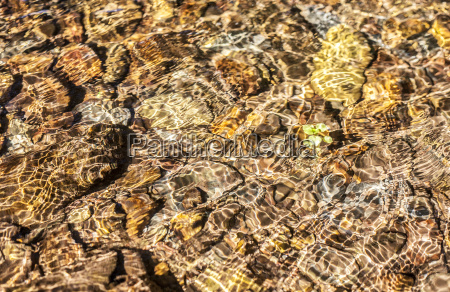 translucent water waves over brown pebbles