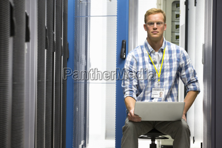 technician with laptop looking at camera