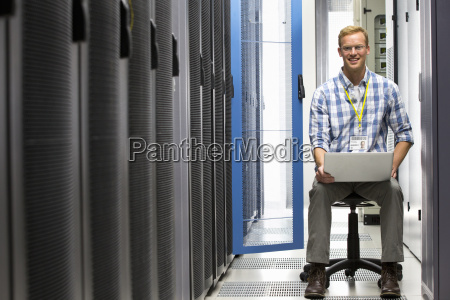 technician with laptop smiling at camera
