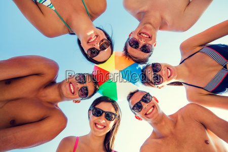 smiling friends in circle on summer