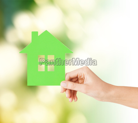 hand holding green paper house