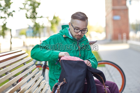 hipster man with backpack sitting on