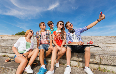 group of smiling friends with smartphone