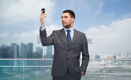 young businessman with smartphone over city