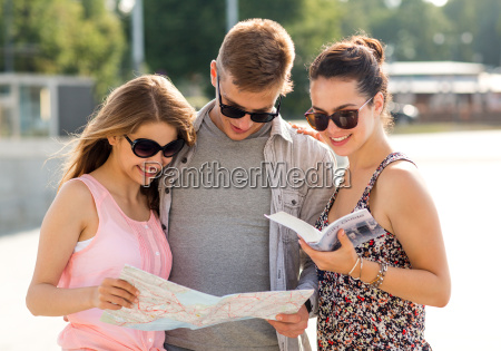 smiling friends with map and city