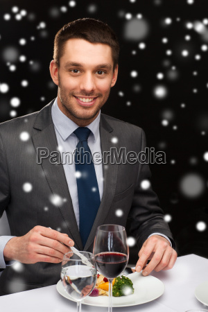 smiling man with tablet pc eating