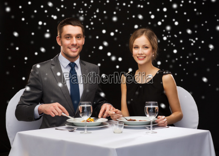 smiling couple eating main course at