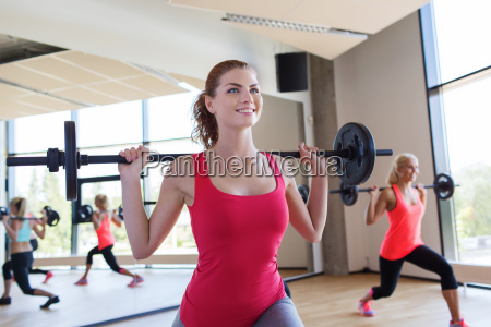 group of women excercising with bars