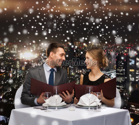 smiling couple with menus at restaurant