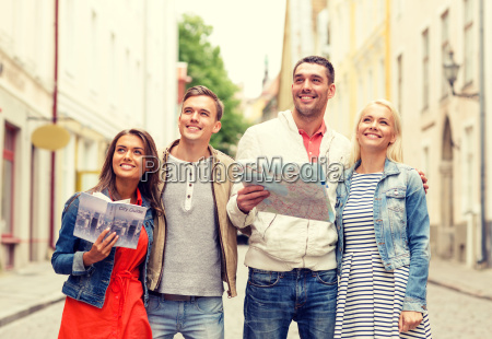 group of smiling friends with city
