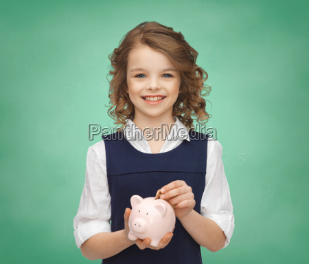 smiling girl putting coin into piggy