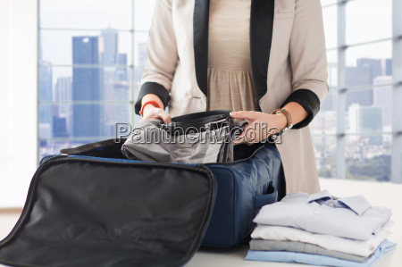 woman packing formal male clothes into