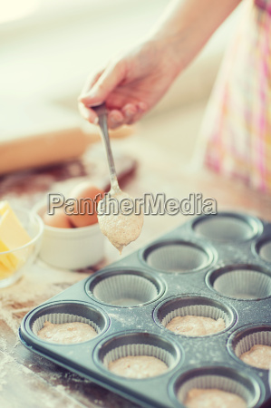 close up of hand filling muffins