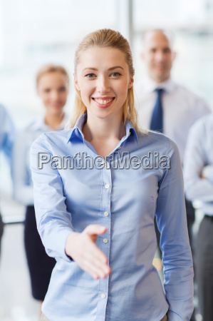 smiling businesswoman making handshake in office