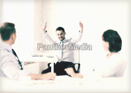 happy businessman showing thumbs up in