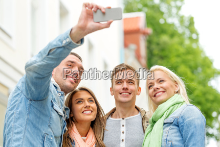 group of smiling friends making selfie