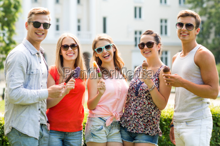 group of smiling friends with ice