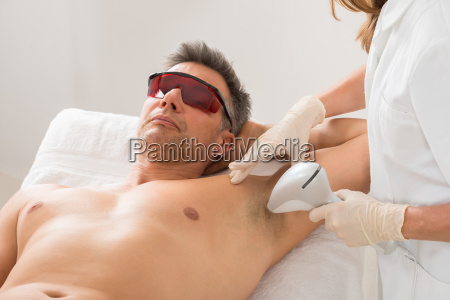 beautician giving hair removal treatment to