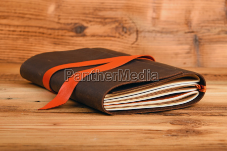 notebook in leather cover on wooden