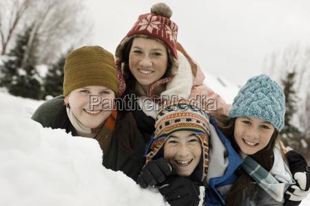 neve invernale quattro bambini raggruppati ridendo