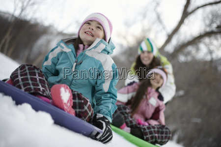 two children playing on sledges on