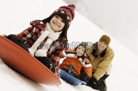 two children riding on sledges across