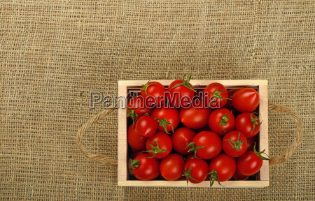 red cherry tomatoes in wooden box
