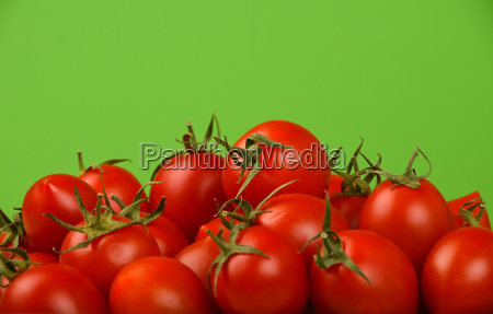 red cherry tomatoes over green background