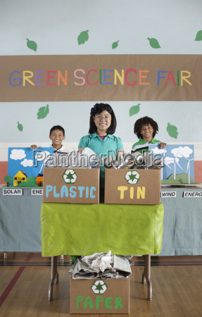 three children standing behind presentations at