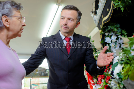 man advising lady on funeral flowers
