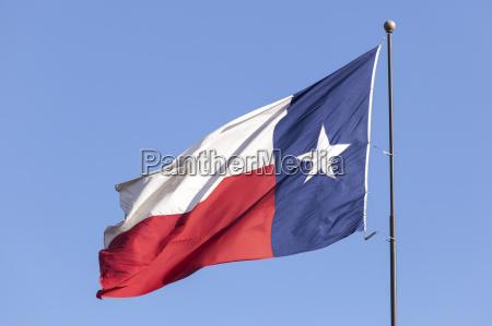 flag of texas against blue sky