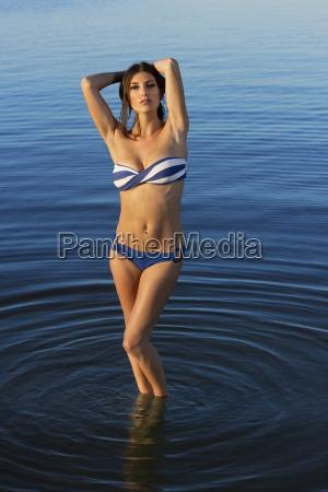 young woman wearing bikini and standing