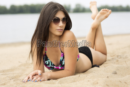 young woman lying on sand at