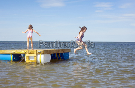 two sisters jumping off floating dock