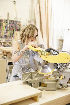 a woman woodworker using a mechanical