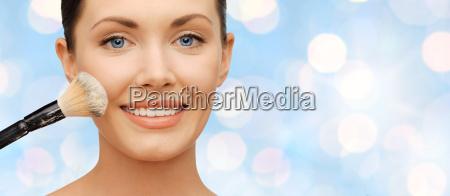 happy woman applying powder foundation with