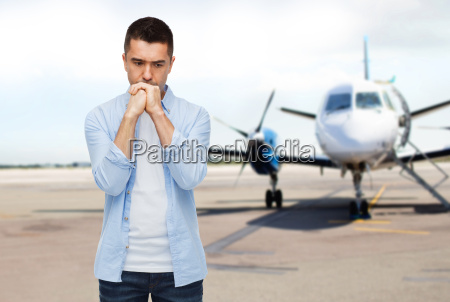 man thinking over airplane on runway