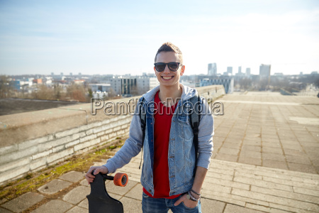 smiling man or teenager with longboard