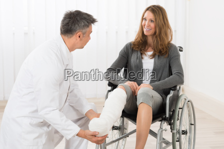 physiotherapist examining leg of patient