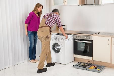 worker repairing washing machine in kitchen