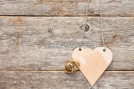 gold wedding rings and paper heart