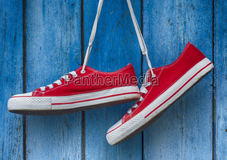 red sneakers hanging on a wooden