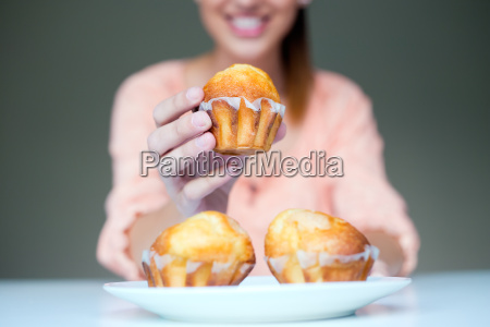 happy young woman eating delicious muffins