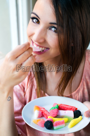 cute young woman eating jelly candies