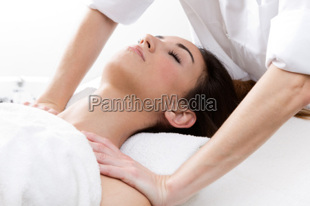 woman enjoying shoulder massage at beauty